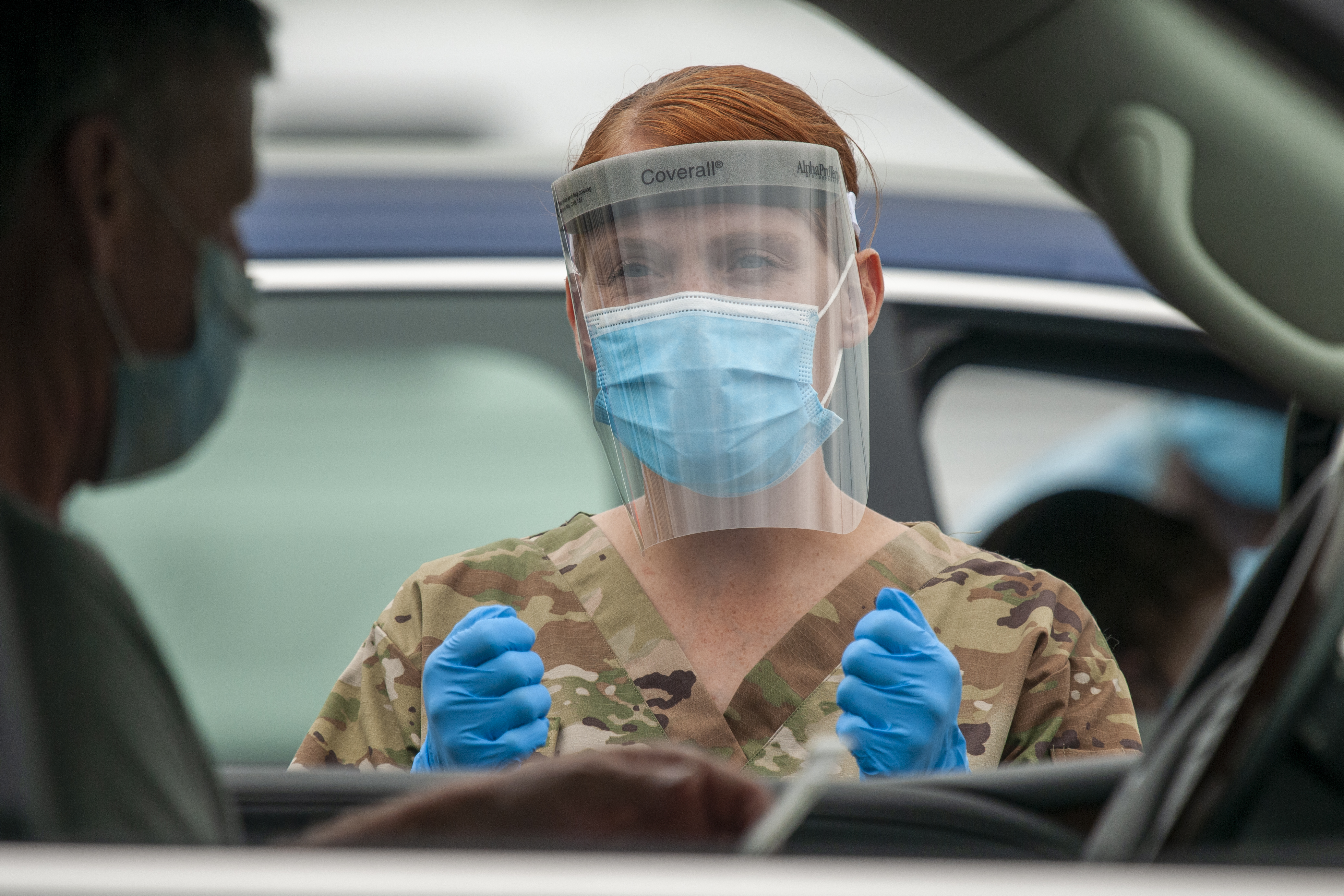 A clinician prepares a patient in car for COVID-19 test