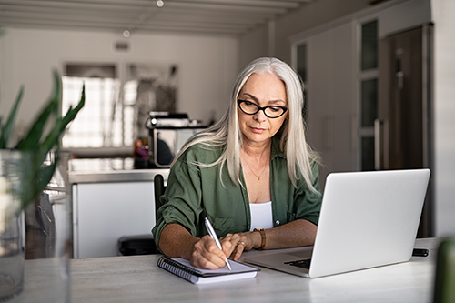 A middle-age woman in front of the laptop.