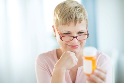 woman looking at a prescription bottle