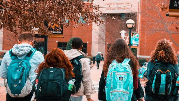 Young adults with backpacks on a college campus.