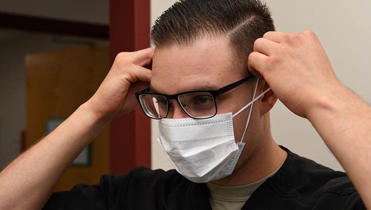 A dental assistant with the 319th Medical Group, demonstrates proper sanitary procedure by putting on a face mask at the medical treatment facility on Grand Forks Air Force Base, N.D. (U.S. Photo by Airman 1st Class Elora J. Martinez)