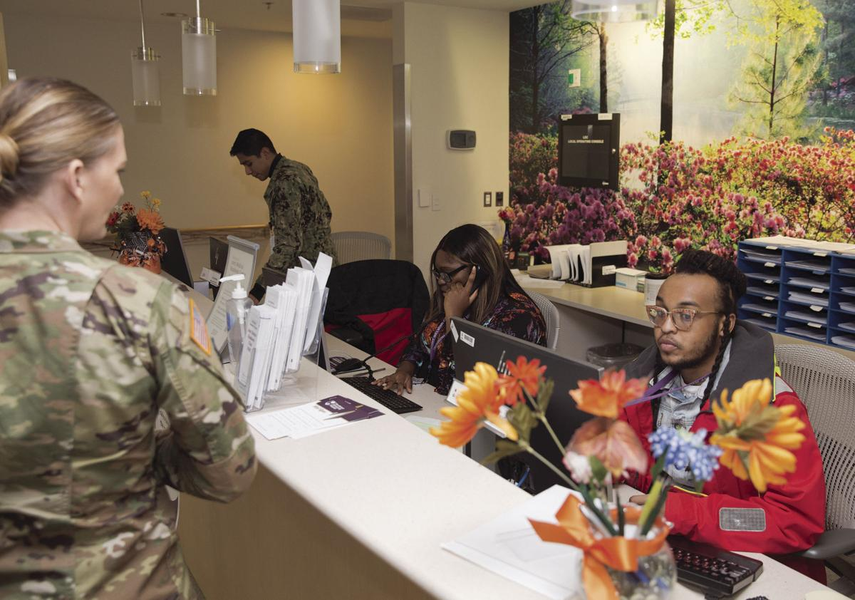 Maj. Kelly Green, Joint Medical Readiness Center department chief, left at the reception desk, Nov. 18.