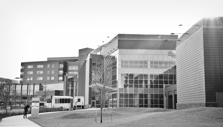 Black and white image looking towards the front of Fort Belvoir Community Hospital from the outside of Meadows Garage